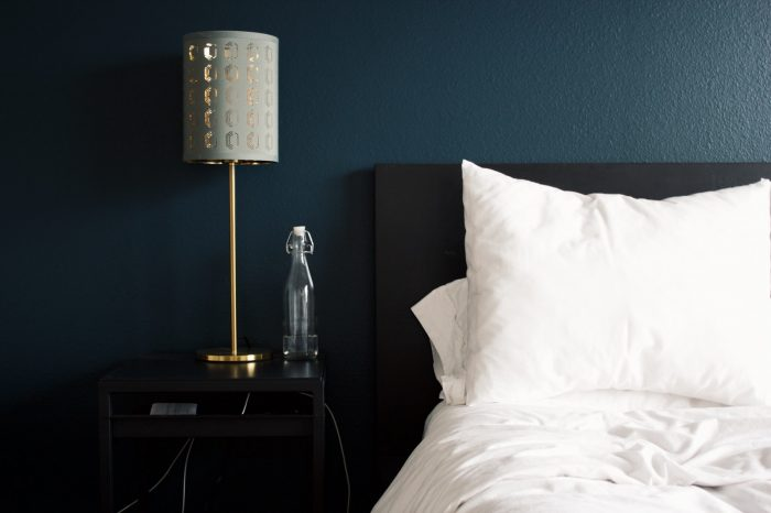 gray table lamp beside white bed pillow